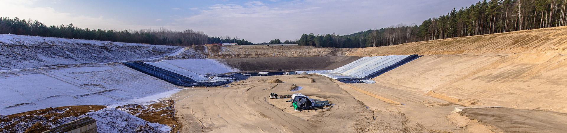 Deponie im Aufbau, riesiges Loch in der Erde mit Spuren von Maschinen im Sand
